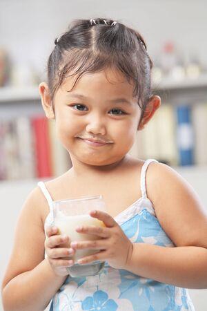 Little Asian girl holding a glass of milk photo