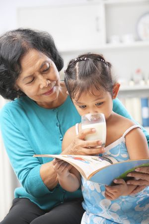Grandma giving milk to her granddaugter while she busy reading book photo