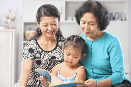 Little Asian girl accompanied by her mother and grandma reading book photo