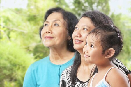 Three Asian female generations looking away at outdoor garden photo