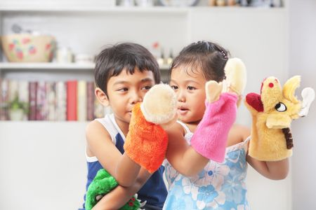 puppets: Asian sibling playing hand mad hand-puppet at home