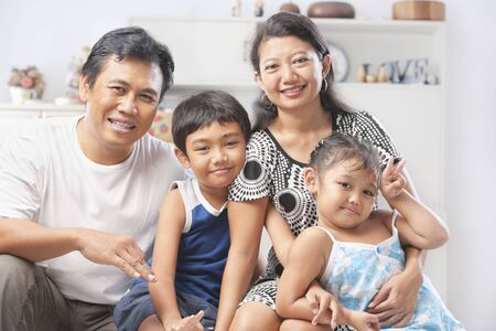Asian family posing at home, with one son and one daughter Stock Photo - 6264341
