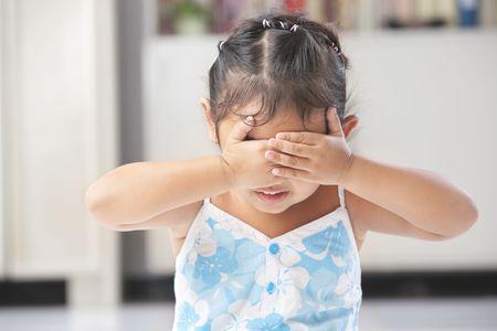 peekaboo: Little Asian girl playing peekaboo or crying Stock Photo