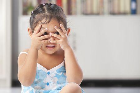 peekaboo: Little Asian girl playing peekaboo in home