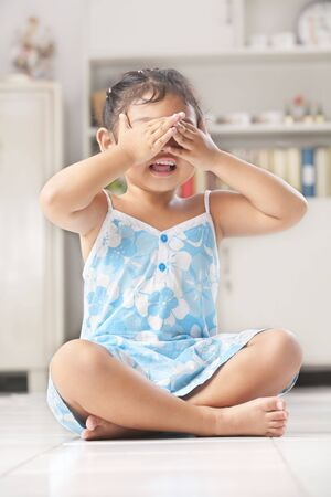 Little Asian girl playing peekaboo or crying photo