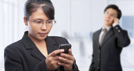 Asian businesswoman use text messaging and businessman on the phone.  photo