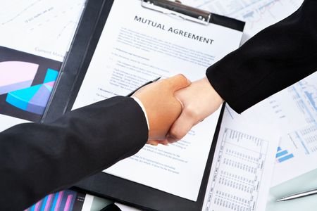 Handshake between businesswomans hand over agreement and other document photo