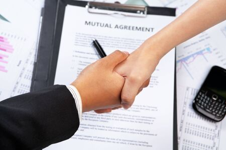 lawyer meeting: Handshake between businesswomans hand over agreement and other document Stock Photo