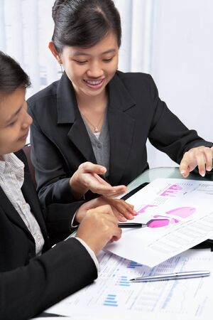 south asians: Two Asian businesswomen, South East Asian and Chinese discussing and teamwork concept
