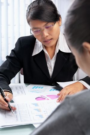 Asian businesswoman showing statistic data to partner or client in oofice photo