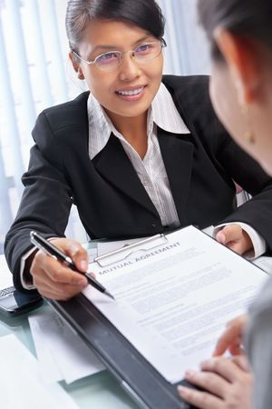 south east asian: Asian businesswoman explaining document to client in the office Stock Photo