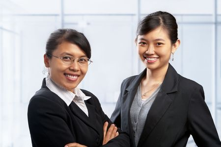 Two Asian businesswoman posing to camera in office photo