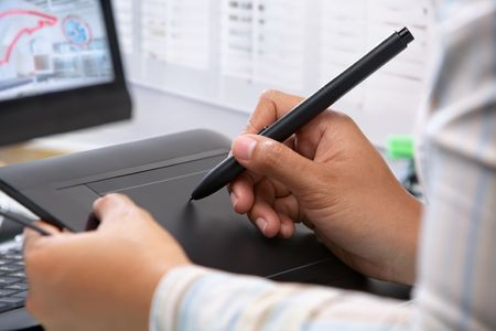 tervező: Graphic designer wotking using pen tablet in office
