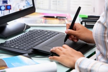 artistas: Dise�ador gr�fico femenina que trabajan en la Oficina utilizando el l�piz de Tablet PC, enfoque selectivo  Foto de archivo