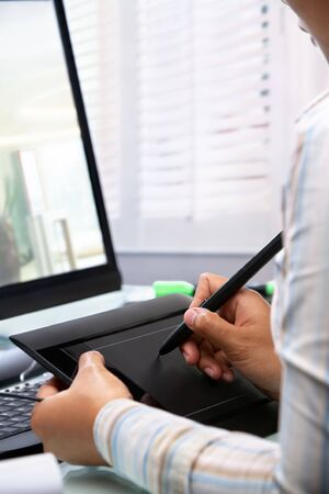 Female graphic designer working in office using tablet pen, selective focus photo
