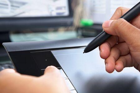 Main en utilisant une tablette numérique pour travailler dans le bureau