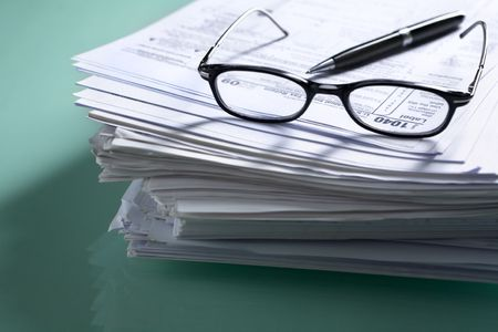 Pile of document with tax form on top, visible though glasses. Focus mainly on 1040. photo