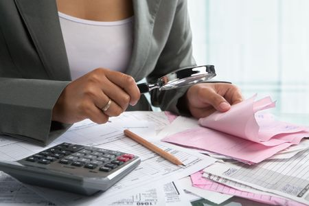 Businesswoman checking bills using magnifying glass in the office