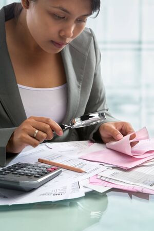 Asian businesswoman checking bills using magnifying glass in the office photo