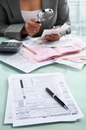 Tax form and unrecognizable businesswoman in the background using magnifying glass photo