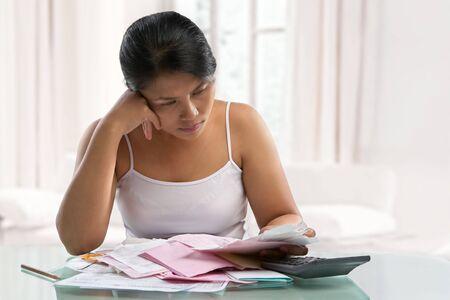 schuld: Aziatische huis vrouw stress over rekeningen en schulden