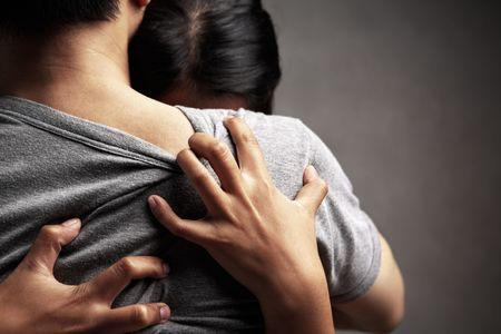 pareja abrazada: Un marido abrazar a su esposa triste, en el tema de fondo oscuro