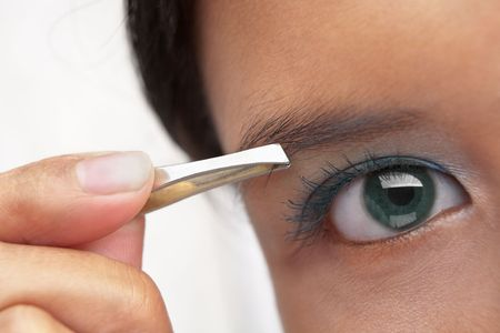 tweezers: A young female using eyebrow tweezers PS:shallow depth of field Stock Photo