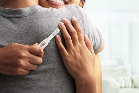 Joyful couple with positive pregnancy shown in the test device Stock Photo