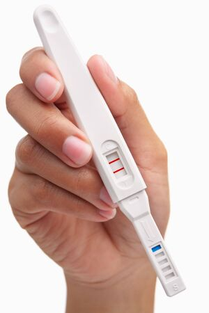 exam results: Hand holding positive result pregnancy test, against white background. You can easily set to negative result by patching the area around the T so only the C area has red strip Stock Photo