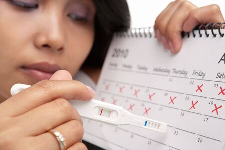 prueba de embarazo: Mujer triste con la prueba de embarazo negativa y calendario. Un concepto que ha podido quedar embarazada