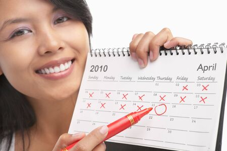 circle calendar date: Woman with red felt tip pen and calendar, actually can be concept to get pregnant from its series, maybe can be used for US tax day