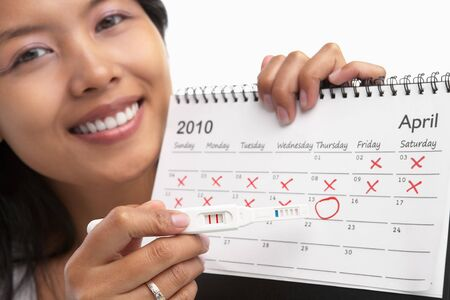 circle calendar date: Happy woman with positive pregnancy test and calendar. A concept being success to get pregnant Stock Photo