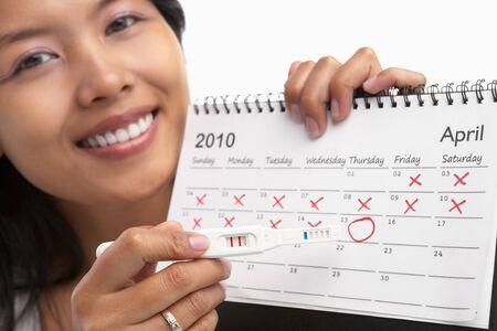 prueba de embarazo: Mujer feliz con la prueba de embarazo positiva y calendario. Un concepto siendo �xito para quedar embarazada Foto de archivo