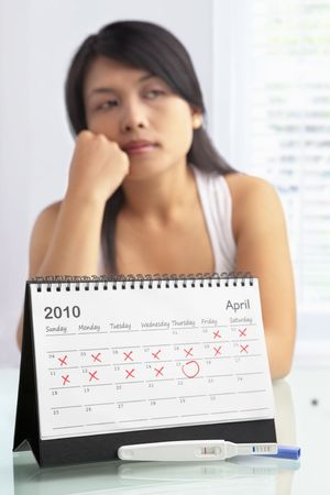 test de grossesse: Sad woman with negative pregnancy test and calendar. A concept being failed to get pregnant