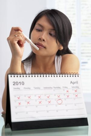 test de grossesse: Femme regardant test de grossesse avec calendrier Banque d'images