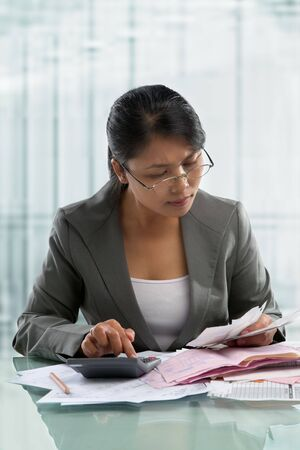 Asian businesswoman checking bills in the office. photo