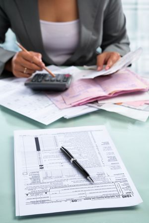 Tax form in front of the table with an accountant on background
