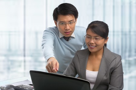 south east asian: Asian business people working together in office Stock Photo