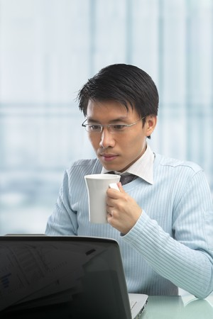 Young Chinese male working in office with laptop photo
