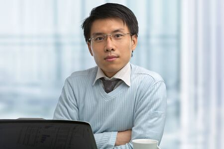 Young Chinese male working in office with laptop Stock Photo - 7283299