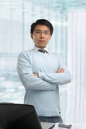 bossy: Young Chinese businessman standing in his office