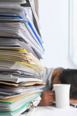 Lots of workload with people sleeping on background. PS: small depth of field and selective focus on papers Stock Photo - 7283246