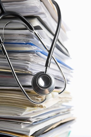 Medical record concept using stethoscope in front of pile of paper. Selective focus photo