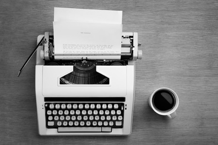 Typewriter with bible script on the paper and a mug of coffee photo