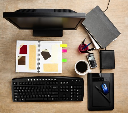 Designer working desk filled with computer, scarpbook and mug of coffee photo