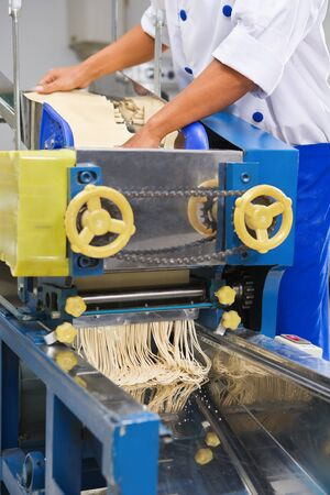 mee: Chef using a machine to cutt the dough into the noodle Stock Photo
