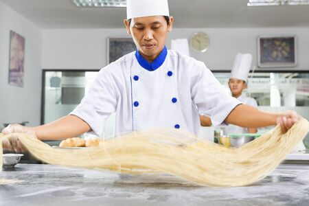 south east asian: Chef making noodle in the kitchen of cooking school. ***PS : selective focus on the noodle with noticable movement blur ***