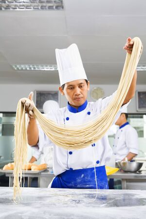 Chef making noodle in the kitchen of cooking school. ***PS : selective focus on the noodle *** photo