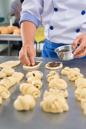 culinary: Chef hand sprinkle the chocolate chips on bread dough. PS: hand movement blur