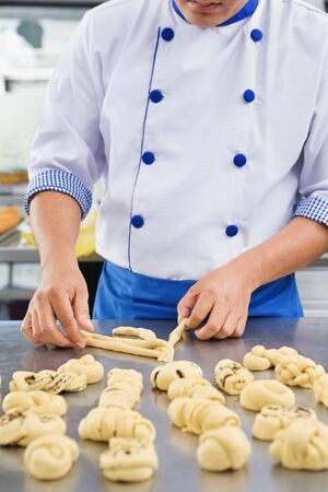haciendo pan: Baker haciendo variaci�n en masa de pan dulce  Foto de archivo